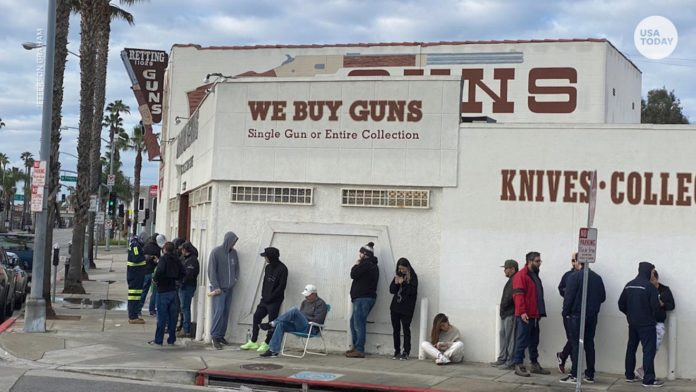 gun buyers form a line outside a gun shop, as background checks get overwhelmed during the pandemic.